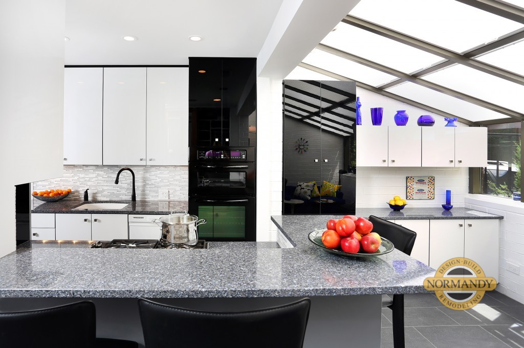 Black and white glossy cabinets in galley kitchen