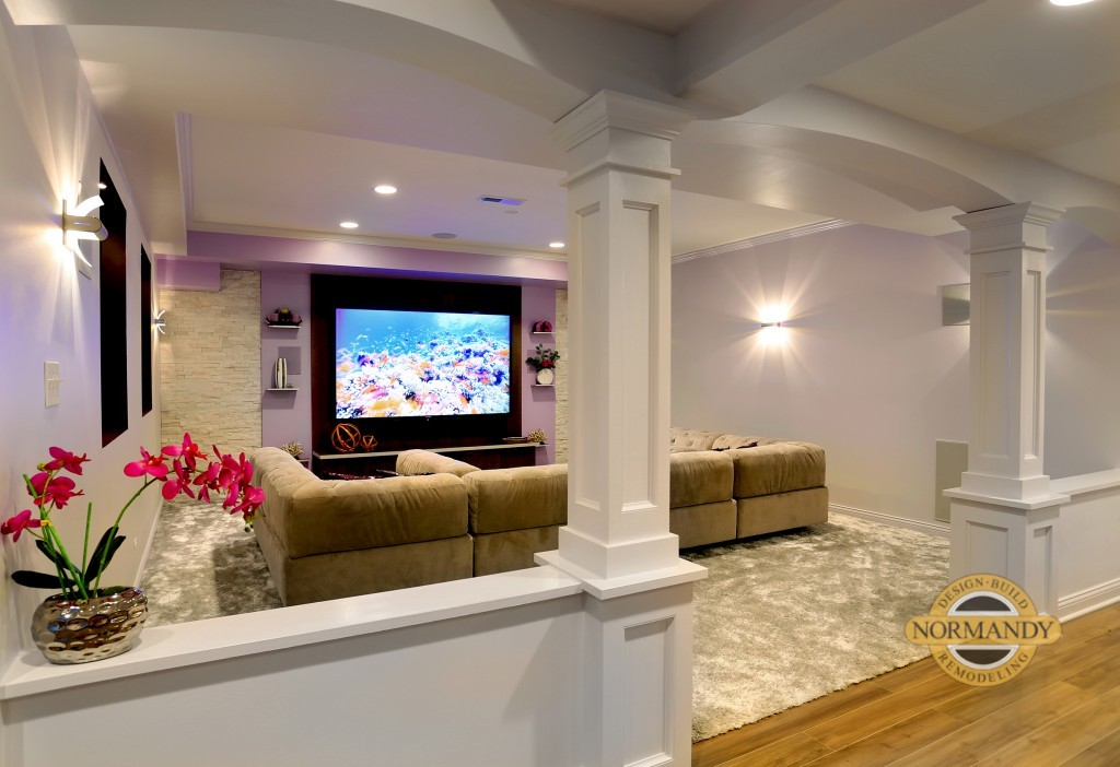 Big screen TV in basement with sectional and decorative columns