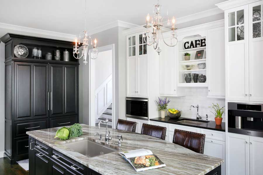 Black and white kitchen with large island, service sink and built in coffee maker