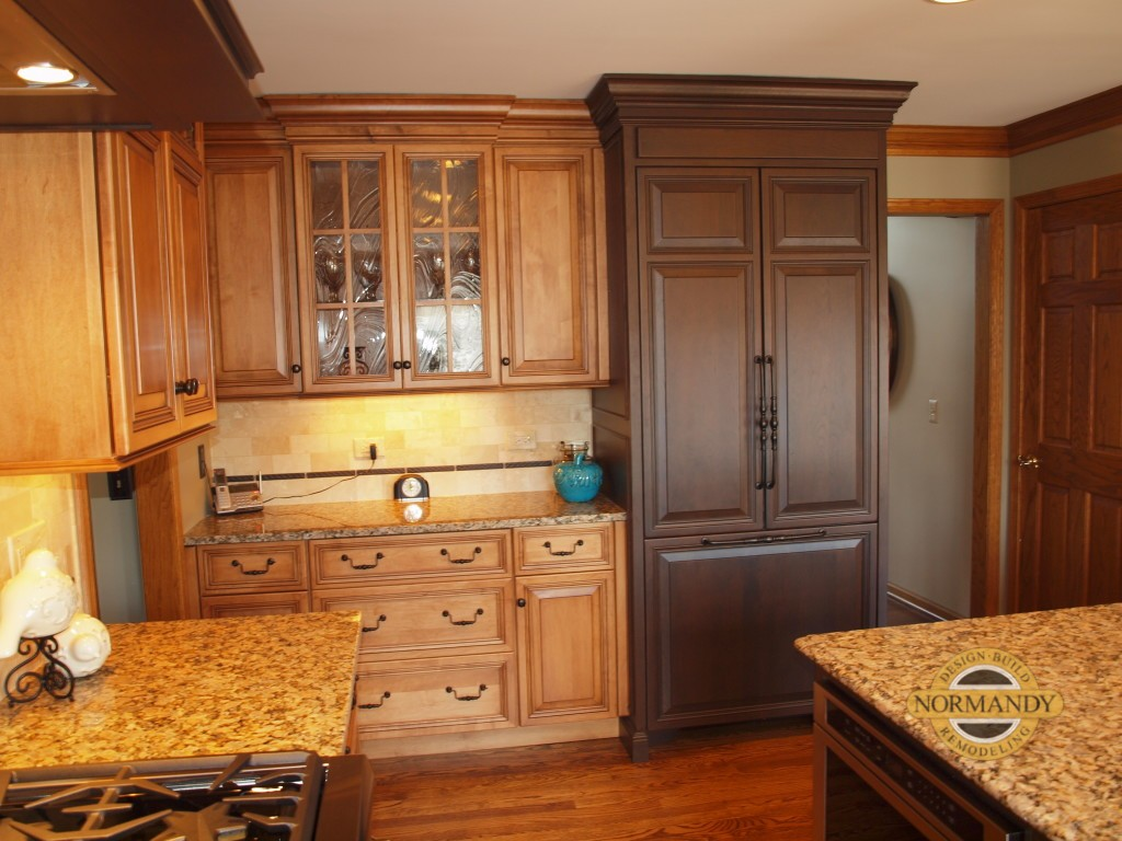 Medium brown stained kitchen with a dark stained refrigerator armoire.