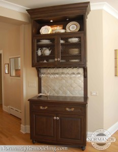 Butler pantry cabinet with wire cabinet fronts, crystal handles, silver backsplash and upside down wine glass storage
