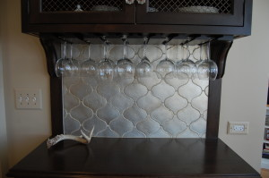 butler pantry cabinet with silver backsplash tile and inverted wine glass storage