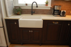 dark stained raised panel cabinets with white apron front sink and crystal knobs and handles.