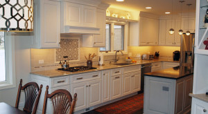 White kitchen with cooktop and taupe backsplash tile