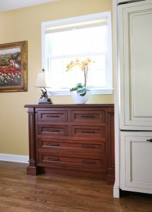 chest of drawers in cherry wood adjoining cream kitchen cabinets