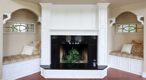 white fireplace mantle with dark stone hearth and surround flanked by a pair of reading nooks