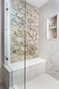 master bathroom shower with exposed stone behind bench