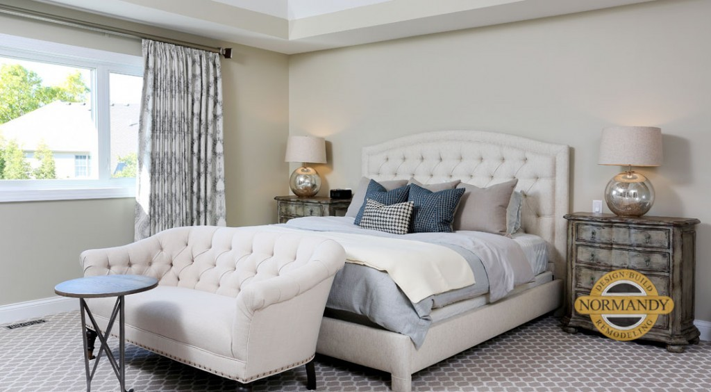 master bedroom with tray ceiling and settee at the end of the bed