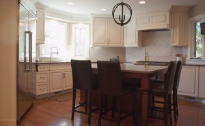 white kitchen cabinets with medium tone wood stained island