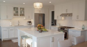 L shaped kitchen with island in white cabinetry with white countertops