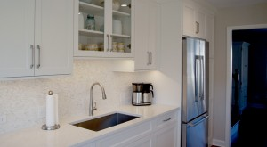 white kitchen cabinetry with a stainless steel single bowl sink