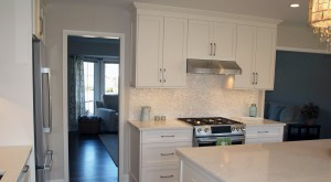 White kitchen cabinetry with a metal hood