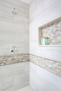 master bathroom shower with decorative tile band and matching storage niche