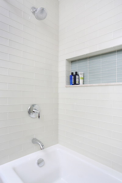 bathtub and shower combination with a colorful tile storage niche
