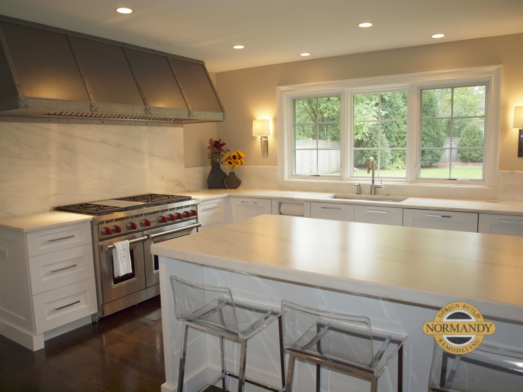 White kitchen with island and professional range