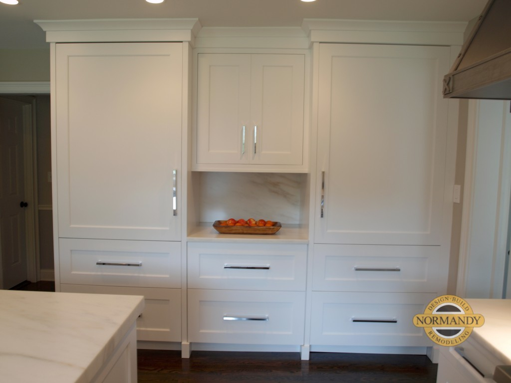 white cabinetry panels disguise refrigerator and freezer