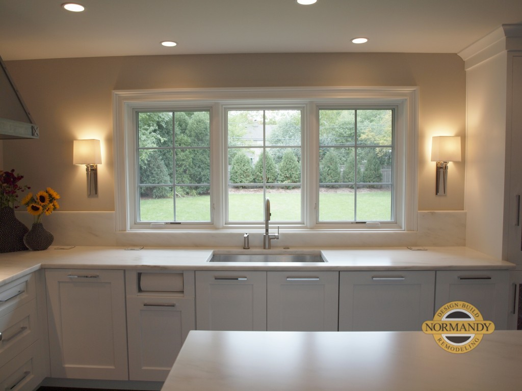 Kitchen sink flanked by decorative sconces and paper towel holder detail