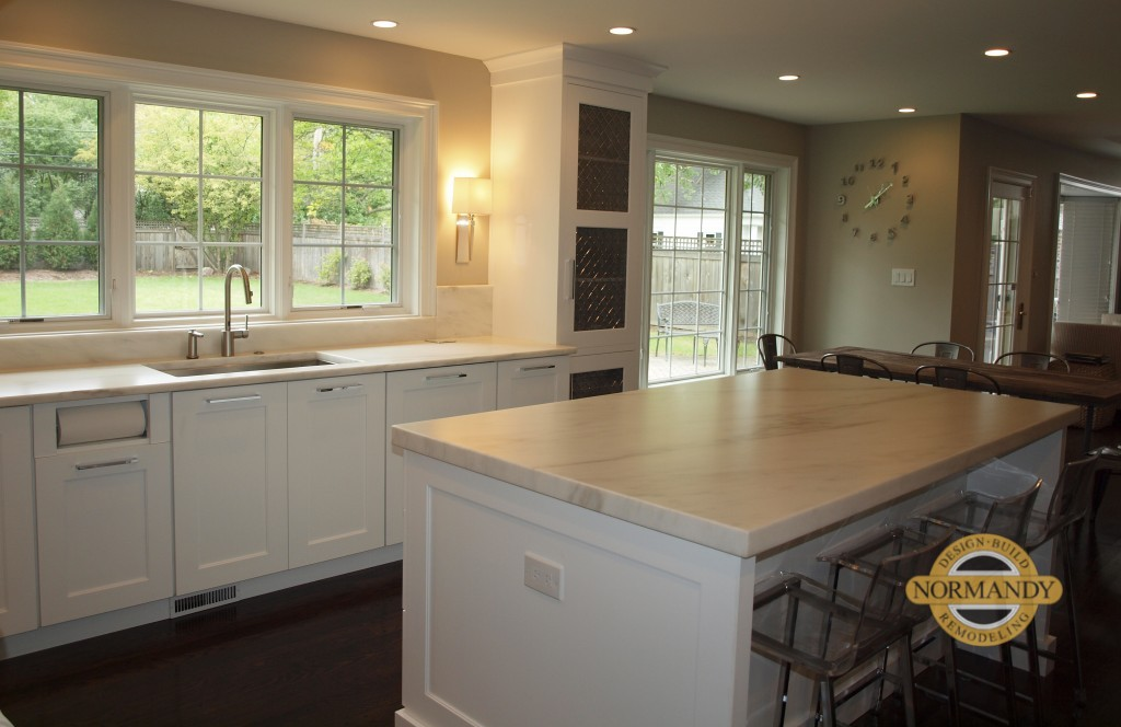White kitchen with large windows and seating at center island
