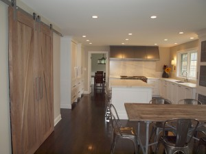 White transitional style kitchen with large silver tone hood and barn doors