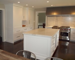 White kitchen with center island and oversized metal hood
