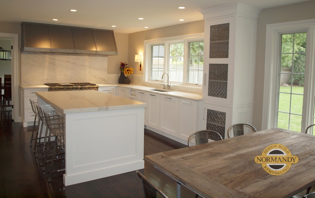 white transitional style kitchen with large windows and oversized metal hood