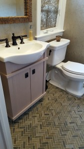 vanity with curved front sink and herringbone tile pattern