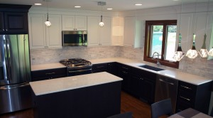 L shaped kitchen with island includes white and dark cabinets