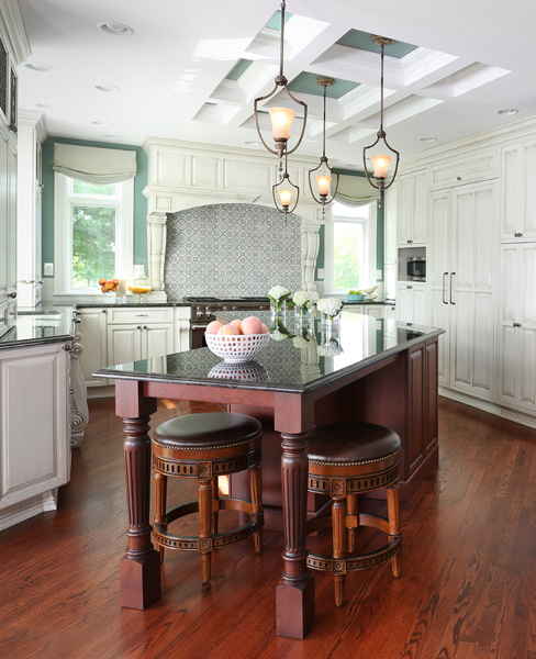 off white painted kitchen with stained island and coffered ceiling