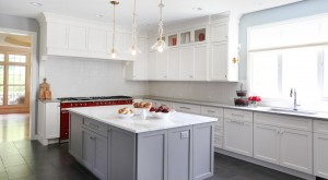 Gray island and red range add interest to this white kitchen