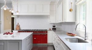 A red stove is the obvious focal point in this white kitchen