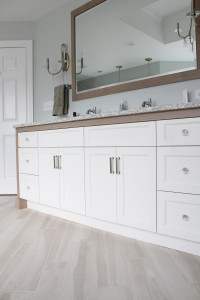 White bathroom vanity cabinets framed with driftwood white oak