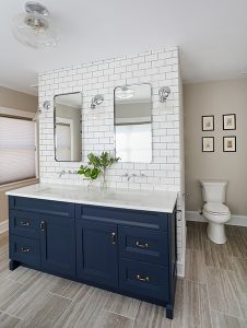 Navy blue master bathroom cabinets with toilet in privacy alcove