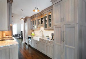 Gray washed wood stain cabinets in a galley kitchen