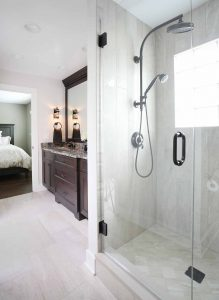 Master bathroom with window in shower and dark stained vanity
