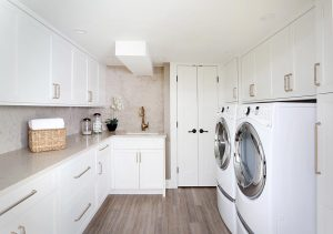 White laundry room cabinets with gold tone fixtures