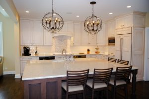 Large center island with dark wood and five seats, white cabinetry