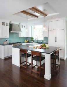 White kitchen cabinets with reclaimed wood beam ceiling and metal hood