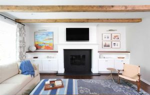 Family room with fireplace and wood beams on teh ceilinjg