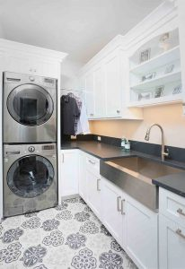 laundry room with stainless steel apron front sink and stacked washer and dryer