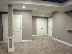 Open Play Area and Storage in a remodeled basement. Carpeting and doors to enclose storage area.