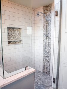 Shower with dual heads, shower reset niche, frameless shower, tile accents. shower bench