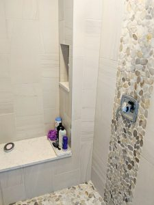 Shower with bench, river rock tile, built in shelf for storage
