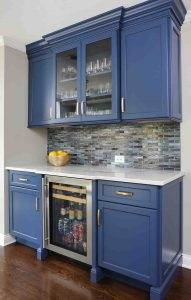 Beautiful Bar area with blue cabinets and accent tile
